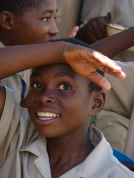 Amidst the green hills of the Matsanjeni, a group of Swazi schoolboys are enjoying their lunch break. They eat (Pap) out of blue plastic bowl and look at me with curiosity. They are intrigued both by the sight of a foreigner and by the camera. A boy smiles. ~ Cindy-Estelle Stauffer